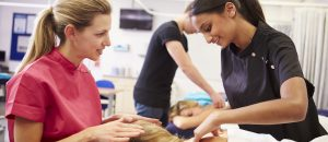 A NYIM massage therapy program instructor teaches a student in Williamsville, NY